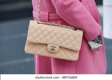 MILAN - FEBRUARY 25: Woman poses for photographers with beige Chanel bag and pink coat before Costume National fashion show, Milan Fashion Week Day 2 street style on February 25, 2016 in Milan.