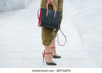 MILAN - FEBRUARY 25: Woman poses for photographers with Louboutin shoes and bag before Costume National fashion show, Milan Fashion Week Day 2 street style on February 25, 2016 in Milan.