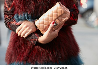 MILAN - FEBRUARY 25: Woman poses for photographers with ancient pink Chanel bag and red fur before Emilio Pucci fashion show, Milan Fashion Week Day 2 street style on February 25, 2016 in Milan.