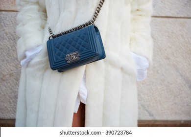 MILAN - FEBRUARY 25: Woman poses for photographers with Chanel blue leather bag and white fur before Cristiano Burani fashion show, Milan Fashion Week Day 2 street style on February 25, 2016 in Milan.