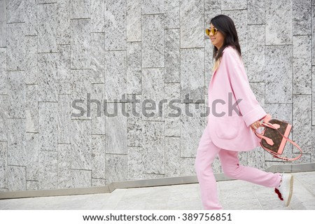 5de956d74 MILAN - FEBRUARY 25: Woman poses walking with pink suit and Louis Vuitton  bag before