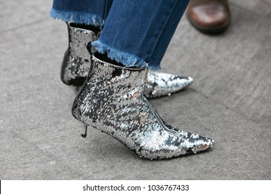 MILAN - FEBRUARY 25: Woman with silver sequin shoes and blue jeans before Emporio Armani fashion show, Milan Fashion Week street style on February 25, 2018 in Milan.