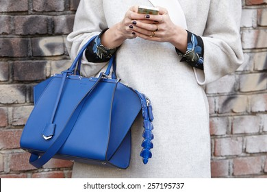 MILAN - FEBRUARY 26: Woman poses for photographers before Fendi show with Fendi blue bag Milan Fashion Week Day 2, Fall/Winter 2015/2016 street style on February 26, 2015 in Milan.