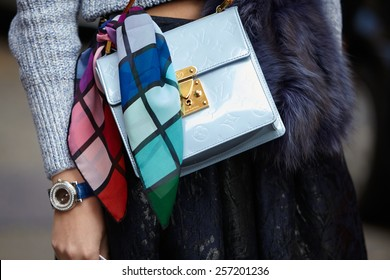 MILAN - FEBRUARY 26: Woman poses for photographers before Anteprima show with blue Louis Vuitton bag Milan Fashion Week Day 2, Fall/Winter 2015/2016 street style on February 26, 2015 in Milan.