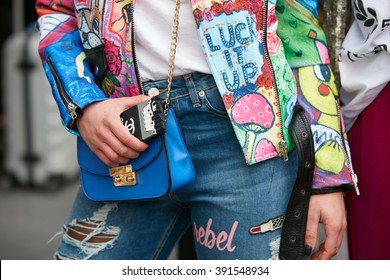 MILAN - FEBRUARY 26: Woman poses for photographers with colorful designed jacket and blue bag before Etro and Iceberg fashion show, Milan Fashion Week Day 3 street style on February 26, 2016 in Milan.