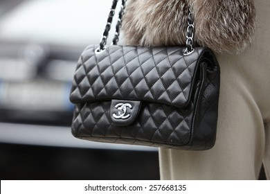 MILAN - FEBRUARY 27: Woman poses for photographers before Emporio Armani show with Chanel bag Milan Fashion Week Day 3, Fall/Winter 2015/2016 street style on February 27, 2015 in Milan.