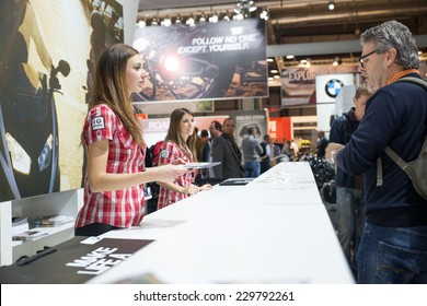 MILAN, IT. NOVEMBER 5, 2014. Hostess giving fliars at bmw motorrad stand at EICMA 2014.BMW Motorrad is the motorcycle brand of the German company BMW.
