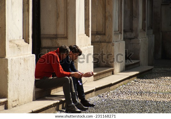 MILAN , ITALY -14 APRIL 2014: two men undefined converse seriously sitting in the public square of the city center