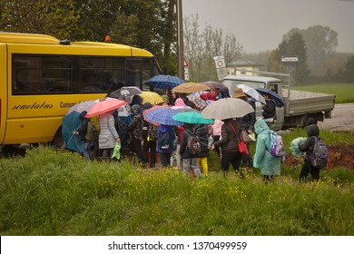 MILAN, ITALY 16 APRIL 2019: School of children on a trip on a gloomy day, intent on climbing into the school bus that accompanies them home.