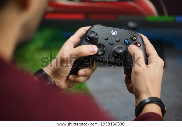 Milan, Italy - 17 March 2021: Microsoft Xbox Series X Gaming Console, Fun and Entertainment Technology, holding the game controller on his hands, play game