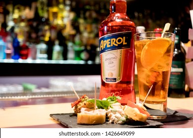 Milan, Italy - 20 april 2019: bottle of italian drink aperol spritz on bar top with traditional italian happy hour aperitivo