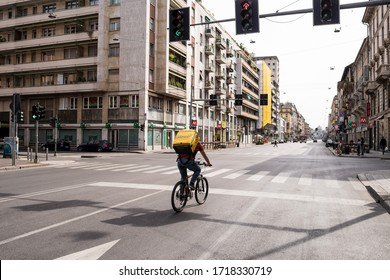 Milan, Italy - 29 April 2020: Due to Coronavirus disease, riders working riding bike on empty street in Milan, Italy to deliver food - Glovo is an International food delivery company.