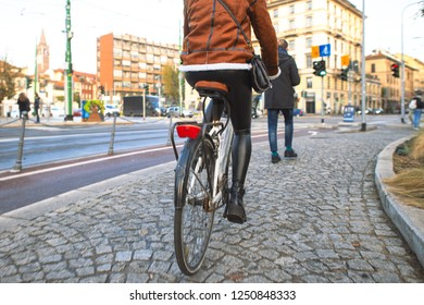Milan Italy 5 December 2018: Woman moves by bicycle on the sidewalks of the city