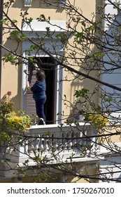 MILAN, ITALY- APRIL 11, 2020:  Woman clean the window shutters on the balcony during coronavirus epidemic period. Daily life in the first phase of lockdown in Lombardy.