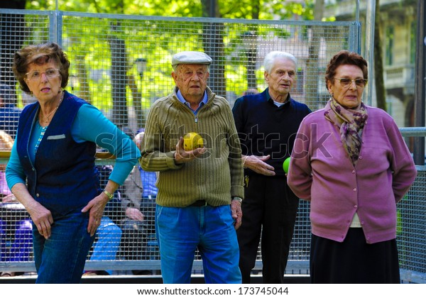 MILAN, ITALY - APRIL 12: Elderly man and women playing bocce together in an outdoor park in Milan April 12, 2011.