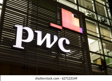 MILAN / ITALY - APRIL 15, 2017: The logo of PricewaterhouseCoopers on the office building of the Italian headquarters in Milan. Nigth view.