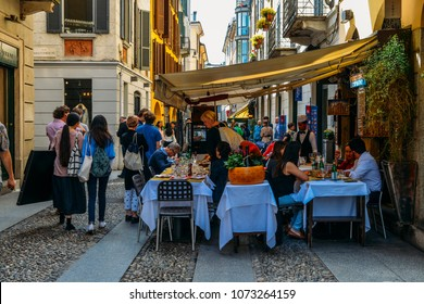 Milan, Italy - April 17, 2018: Tourists on pavement strolling in historic part of town with many restaurants and bars