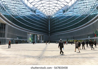 Milan, Italy - April 18, 2016: People walking in the indoor square of Palazzo Lombardia, a complex of building in the centre of Milan.