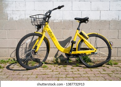 Milan, Italy - April 20, 2019: A broken yellow Ofo share bike abandoned on a street. Ofo interrupted the service in Milan for vandalism against his bicycles.