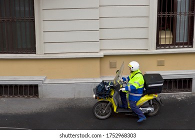 MILAN, ITALY- APRIL 20, 2020:    mailman on a motorcycle deliver the mail  during coronavirus epidemic period.Mail delivery at the door. Daily life in the first phase of lockdown in Lombardy.