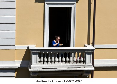 MILAN, ITALY- APRIL 22, 2020:  Woman eat his meal  on the balcony during coronavirus epidemic period. Daily life in the first phase of lockdown in Lombardy.