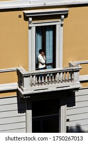 MILAN, ITALY- APRIL 24, 2020:  Woman smoke standing on the balcony during coronavirus epidemic period. Daily life in the first phase of lockdown in Lombardy.