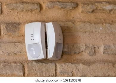 Milan, Italy - April 25, 2018: two alarm pir sensors installed on a face-facing brick wall