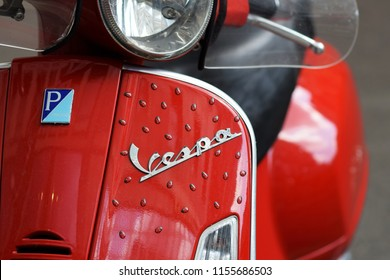 MILAN, ITALY - Aug 11 2018: Close up detail of elegantly designed red Vespa Italian scooter logo with ladybug 3D stickers parked in a street at Milan. Vespa is a Piaggio production scooter.