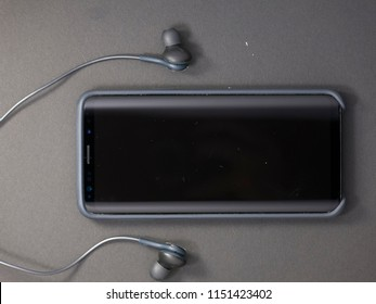 Milan, Italy - August 2, 2018: close up on black AKG headphones and a Samsung Galaxy S9 smart phone, resting on a black background, no people are visible