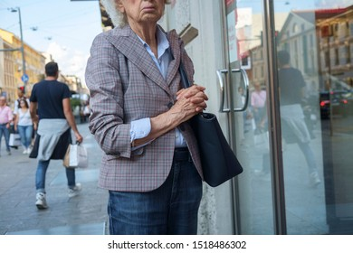 Milan, Italy, August 2019. Elderly woman in front of a shop in a central street of the town.