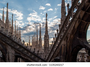 Milan / Italy — August 3, 2010: Roof terrace of Milan Cathedral (Duomo) with its spires and sculptures, seen at sunset. Duomo di Milano is the famous for its beautiful gothic architecture