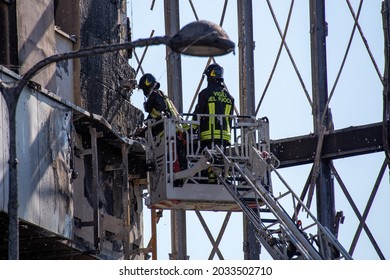 """Milan, Italy - August 30, 2021: Italian firefighters in action during an emergency to extinguish the massive fire of the """"Torre dei Moro"""" skyscraper in via Antonini."""