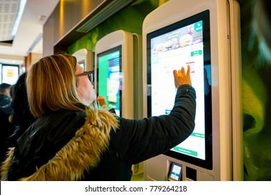 MILAN, ITALY - CIRCA NOVEMBER, 2017: customers at a McDonald's store place orders and pay through self ordering kiosks.