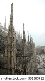 Milan, Italy. CIRCA OCTOBER 2014. Architecture details of gothic cathedral, Milan Cathedral, and people moving on Piazza del Duomo.
