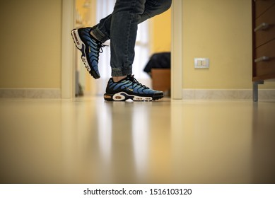 Milan, Italy - December 1, 2018: Young man wearing Nike Air Max Plus TN Hyperblue shoes at home - illustrative editorial
