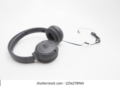Milan, Italy - December 11, 2018: close up on JBL headphones resting on a white background.