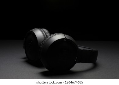 Milan, Italy - December 11, 2018: close up on JBL headphones resting on a black background.