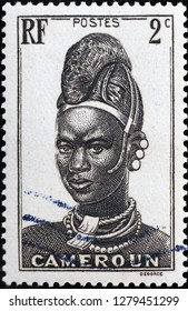 Milan, Italy – December 11, 2018: Woman portrait on vintage stamp of Cameroon