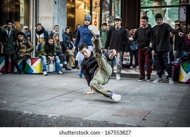 MILAN, ITALY - DECEMBER 14: breakdancers in downtown Milan on December, 14 2013: a group of performer guys breakdencers dancing in the center of Milan attracting hundreds of people