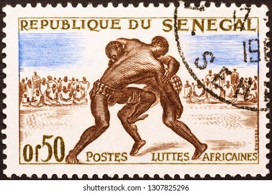 Milan, Italy – December 16, 2014: African wrestlers on old postage stamp of Senegal