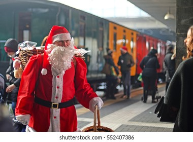 MILAN, ITALY - DECEMBER 17, 2016: Father Christmas welcomes people at station Porta Garibaldi with colorful vintage train in the background