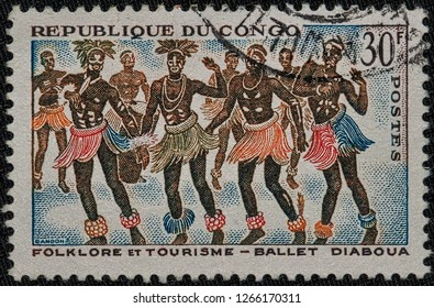 MILAN, ITALY - DECEMBER 23, 2018: A stamp of Republic of Congo shows a folkloric ballet, circa 1964. Stamp with postmark.