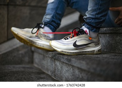 Milan, Italy - December 27, 2018: Young man wearing a pair of Nike Air Max 97 Off-White shoes in the street - illustrative editorial