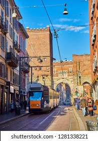 Milan, Italy - December 29, 2018. A tram crossing Corso di Porta Ticinese street with the Antica Porta Ticinese in the background. Milan, Lombardy, Italy.