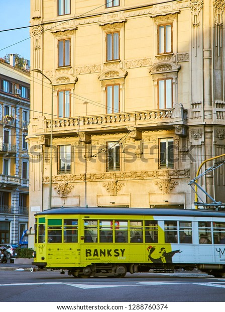 Milan, Italy - December 29, 2018. A tram advertising a monographic exhibition of Banksy crossing Via Giovanni Boccaccio, a street of Zona Magenta neighborhood in the downtown of Milan, Lombardy.