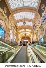 Milan, Italy - December 30, 2018. Travellers in the main hall, antique Sala della Biglietteria, of the Milano Centrale train station. Milan, Lombardy, Italy.