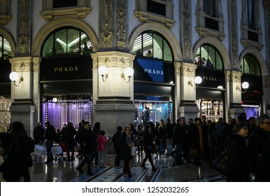 Milan, Italy - December 7, 2018: Crowd of people and tourists shop for Christmas in front of the shop windows of the PRADA luxury boutique store in Galleria Vittorio Emanuele II gallery at night