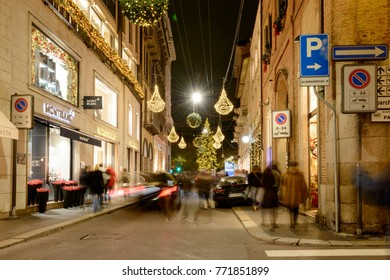 MILAN, ITALY - DECEMBER 7: luxury cars among people under Xmas lights  in Montenapoelone street in the  luxury fashion shopping precinct, shot on patron saint evening, dec 7 2017, Milan, Italy