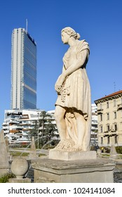 Milan, Italy - Feb 13, 2018: Juxtaposition of statue at Fountain of the Four Seasons in Piazza Giulio Cesare, Citylife, with Il Dritto  skyscraper in  background