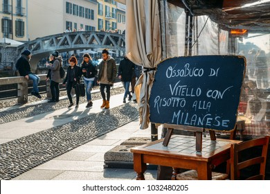 Milan, Italy - Feb 24, 2018: Sign at restaurant advertising a local Milanese dish of bone marrow and yellow safron risotto rice on the Naviglio Grande canal, an alternative neighbourhood in the city